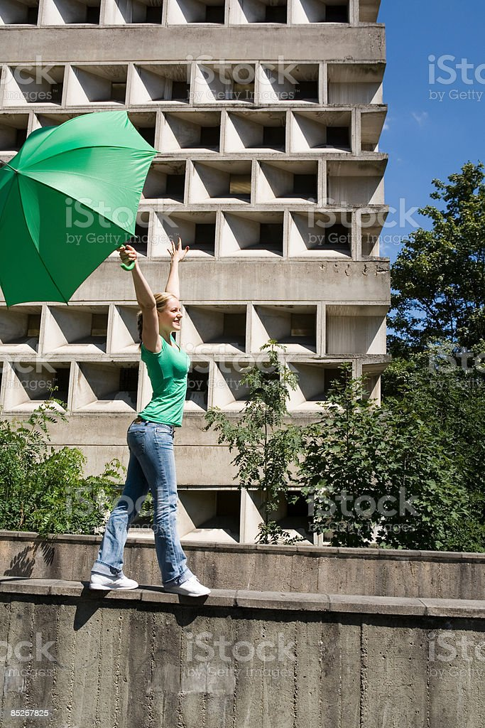Young woman on wall with umbrella royalty-free stock photo