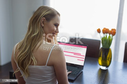 1151920695 istock photo Young woman online chat on laptop looking over shoulder 1128028696