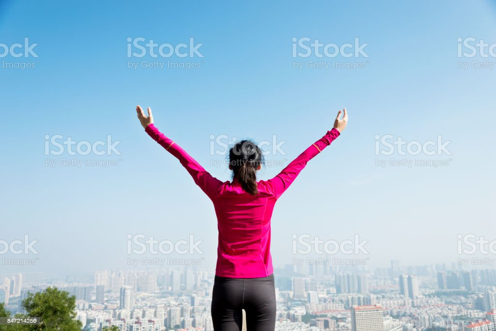 Young woman open arms on mountain peak.