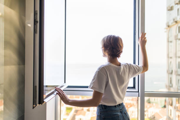 young woman open window in the morning at home - open window imagens e fotografias de stock