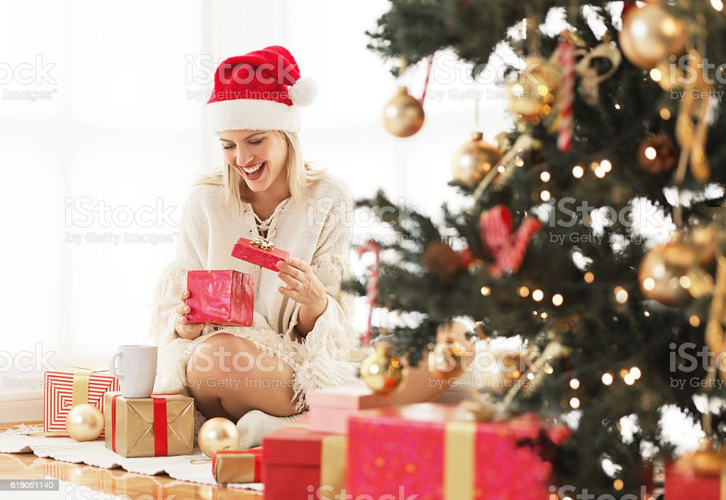 Young woman opening a present on Christmas morning stock photo