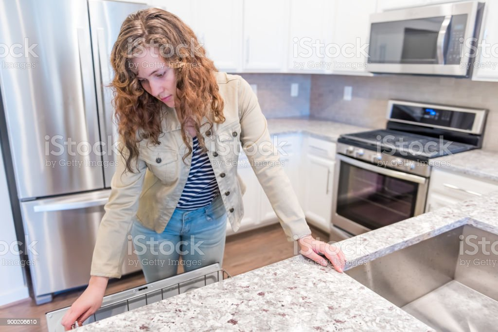 Image of: Young Woman Opening Inspecting Dishwasher In Modern Gray Brown Kitchen Features Cabinets With Granite Countertops And Tile Backsplash With Stove Oven Stock Photo Download Image Now Istock