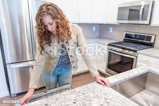 istock Young woman opening inspecting dishwasher in modern gray, brown kitchen features cabinets with granite countertops and tile backsplash with stove oven 900206610