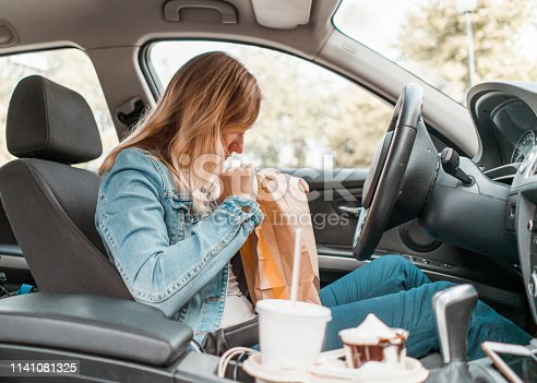 Young woman sitting in her car, opening a take out bag, eating fast food and drinking soda and coffee. In a rush, multi tasking, eating take out burger, french fries and dessert while driving a car.