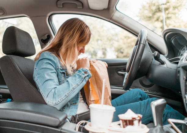 Young woman opening take out food bag in a car stock photo