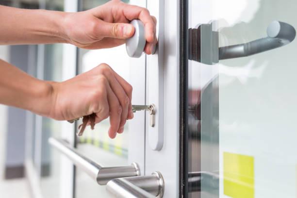 jovencita abriendo la puerta principal de su edificio de apartamentos - cerradura fotografías e imágenes de stock