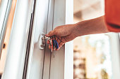 istock Young woman opening the front door of her apartment building 1272767784