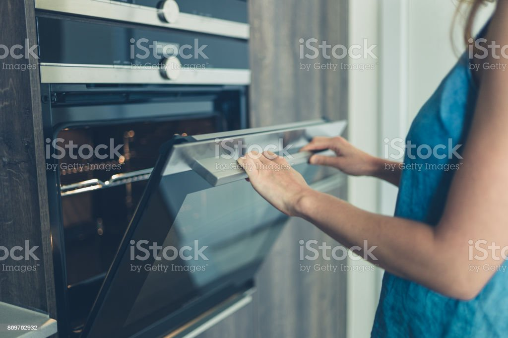 Young woman opening the oven stock photo