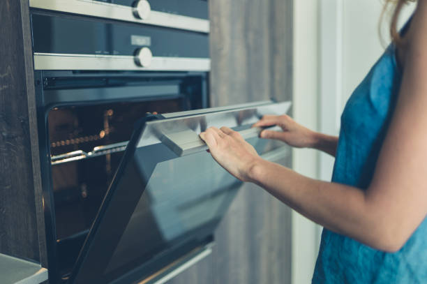 Young woman opening the oven A young woman is opening the oven in her modern kitchen oven stock pictures, royalty-free photos & images