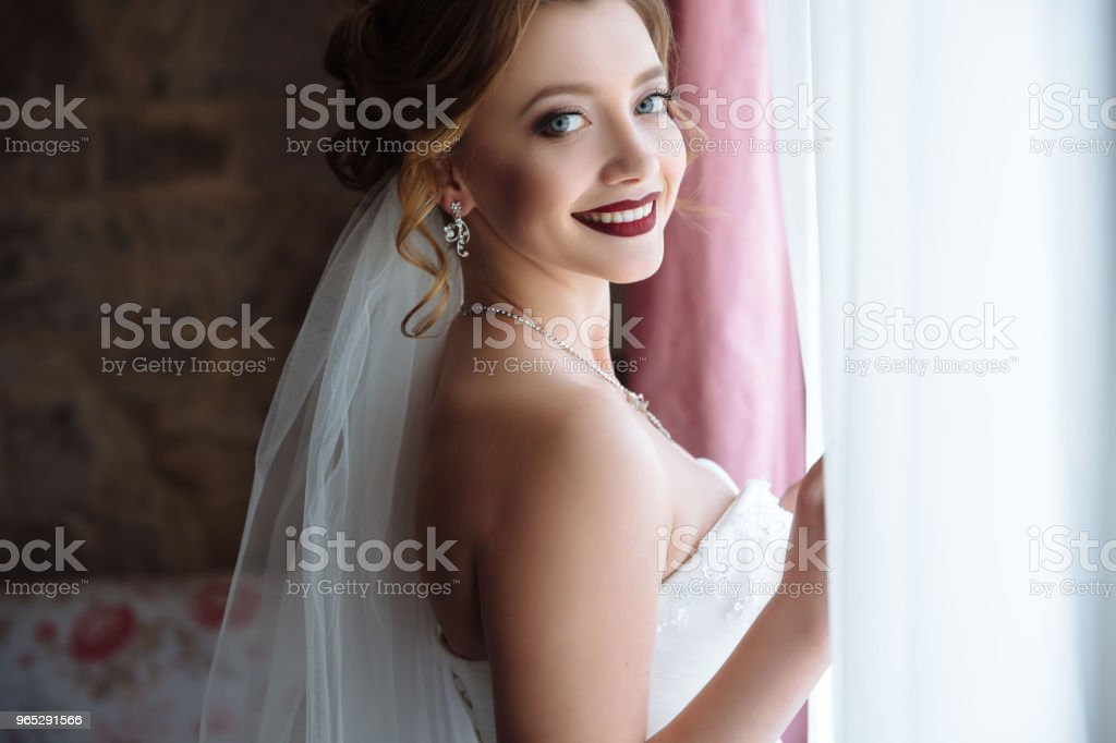 A young woman opens the curtains. She looks very happy because she is getting married. Beautiful smile girl with dark lipstick. Morning of bride at wedding day, preparations zbiór zdjęć royalty-free
