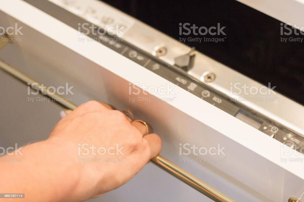A young woman opens the lid of a dishwasher for washing dishes royalty-free stock photo