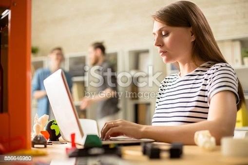 886646936 istock photo Young Woman Operating 3D Printer 886646980