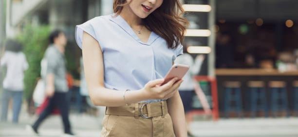 スマートフォンを操作する若い女性 - 女性 手 ストックフォトと画像