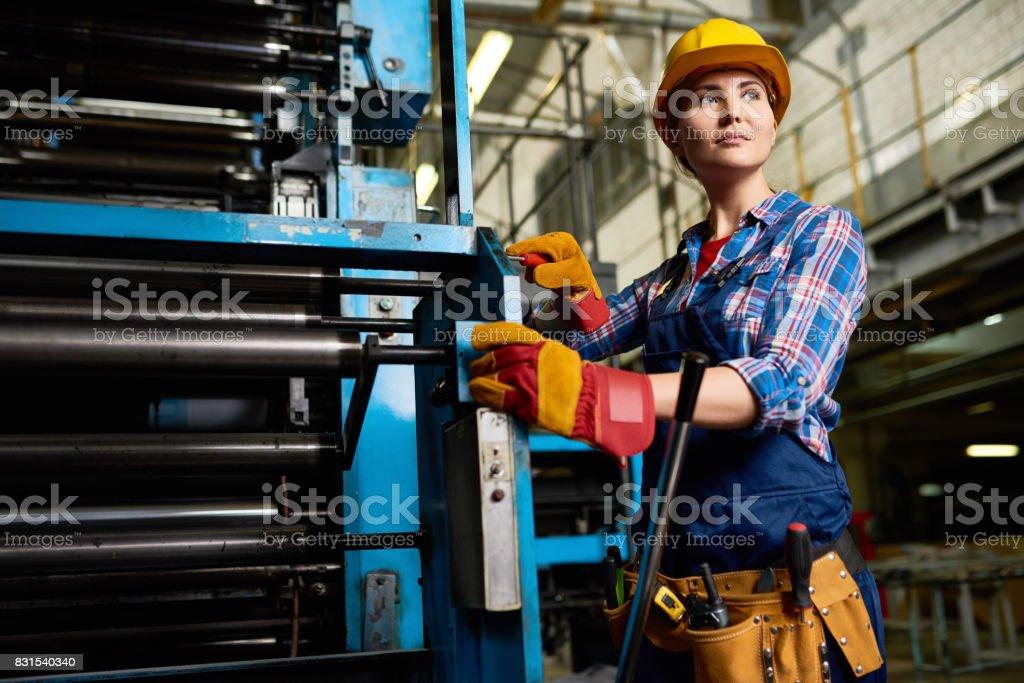 Junge Frau, die Maschine Bedieneinheiten in Werkshalle – Foto