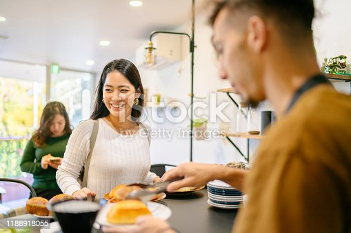 597640822 istock photo Young woman ordering food and drink at cafe 1188918055