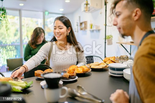 597640822 istock photo Young woman ordering food and drink at cafe 1188918729