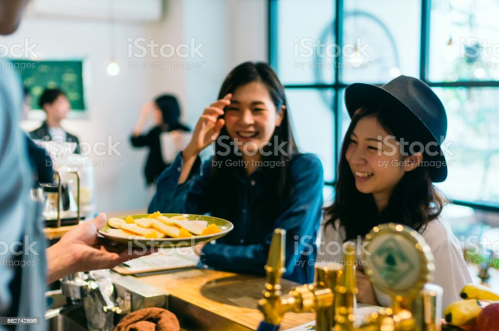 2 young woman ordering food at cafe stock photo