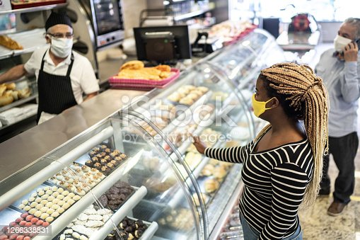 Young woman ordering some groceries in the bakery