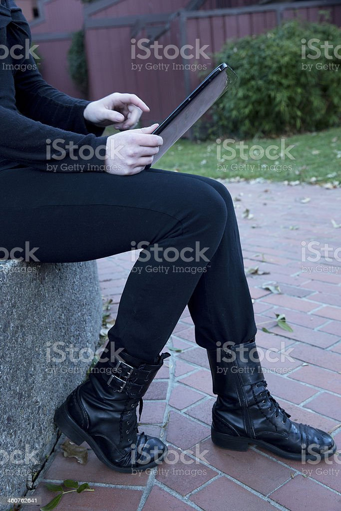 young woman outdoors on digital tablet royalty-free stock photo