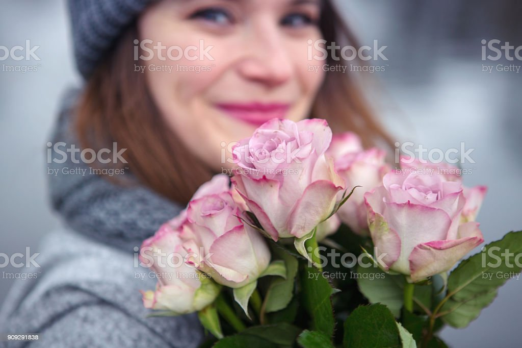 young woman outdoors with bouquet of pink roses стоковое фото