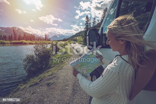 841604240 istock photo Young woman outside van looks at road map 841680734