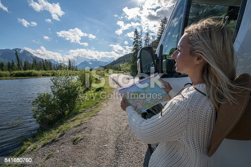 841604240 istock photo Young woman outside van looks at road map 841680760