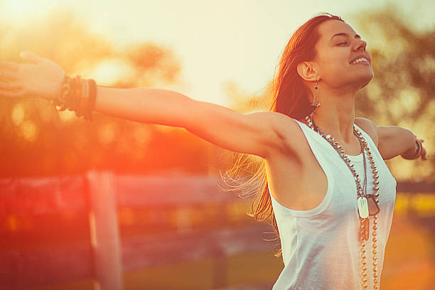 young woman outstretched arms enjoys the freedom and fresh air - arms outstretched stock photos and pictures