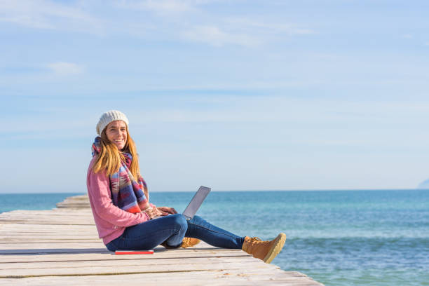 Young woman over pier working with her laptop stock photo
