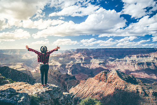 A dramatic overlook over the grand canyon in arizona USA. A Young woman looks over the edge in amazement.