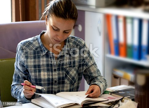 istock Young woman overwhelmed by work 1139895862