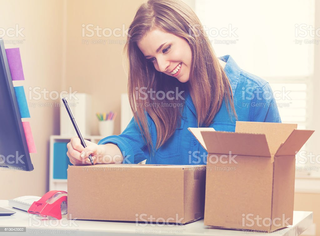 Young woman packing boxes to be shipped stock photo