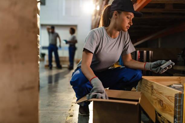 jonge vrouw verpakkingsproducten tijdens het werken in industrieel magazijn. - warehouse worker stockfoto's en -beelden