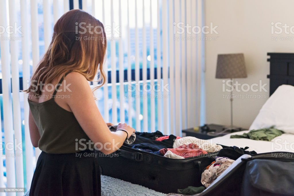 Young woman packing suitcase in bedroom. stock photo