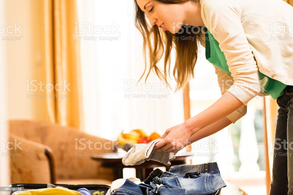 Young woman packing suitcase on bed stock photo