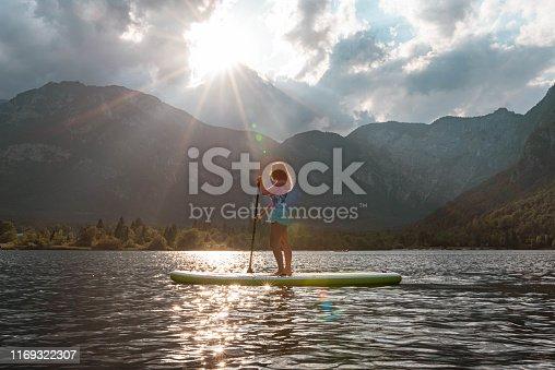 Young woman paddleboarding on the lake Bohinj.