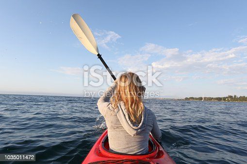 Young woman paddles kayak in the morning near Vancouver, B.C.