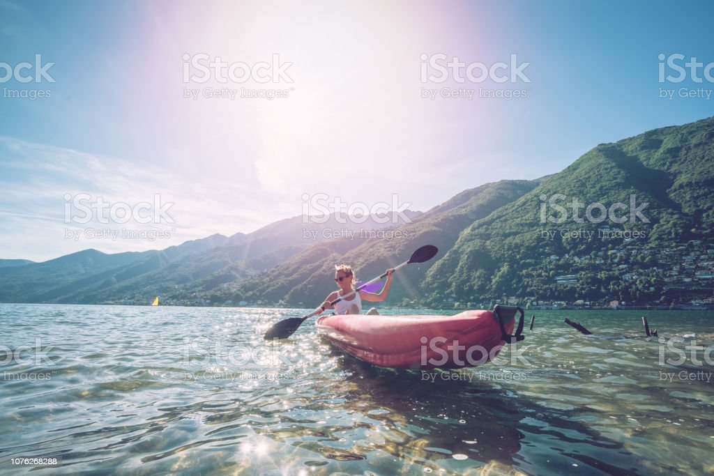 View of a young woman canoeing on beautiful mountain lake in...