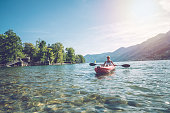 View of a young woman canoeing on beautiful mountain lake in Switzerland. \nInflatable red canoe on water with mountain scenery\nPeople travel outdoor activity concept
