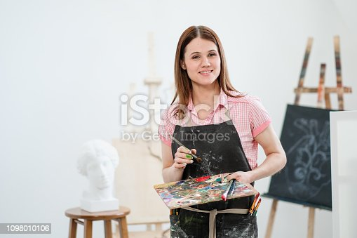 629775804 istock photo A young woman painter in a bright white studio draws a picture on canvas on an easel. 1098010106