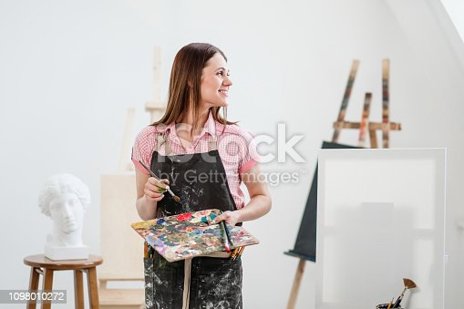 istock A young woman painter in a bright white studio draws a picture on canvas on an easel. 1098010272
