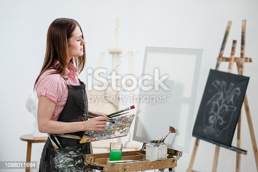 istock A young woman painter in a bright white studio draws a picture on canvas on an easel. 1098011694