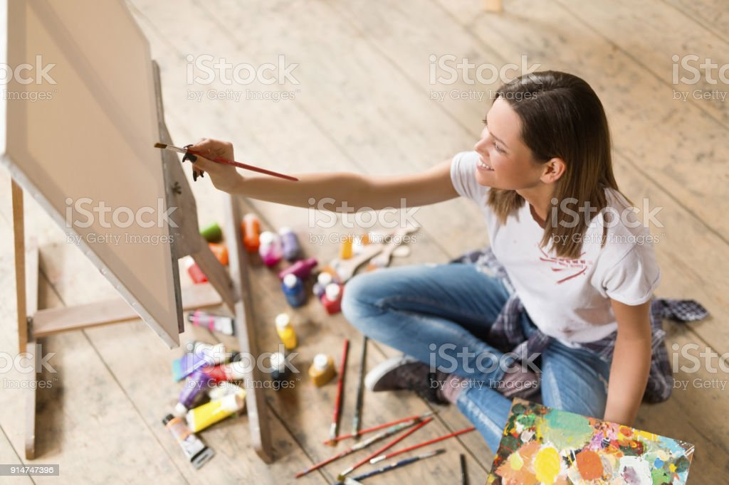 Young woman painting on canvas
