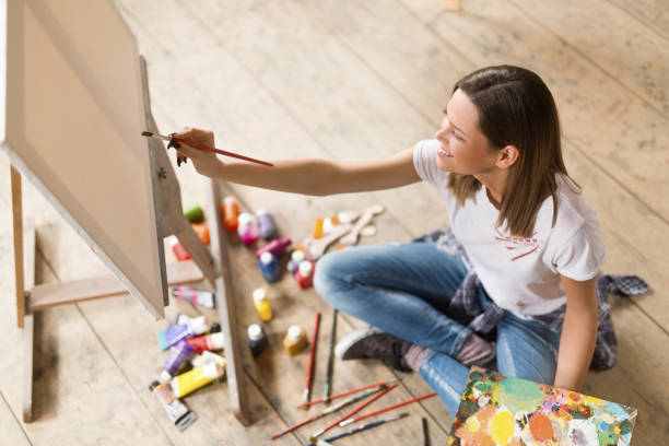 Young woman painting on canvas Young woman sitting on the floor and painting on canvas hobbies stock pictures, royalty-free photos & images
