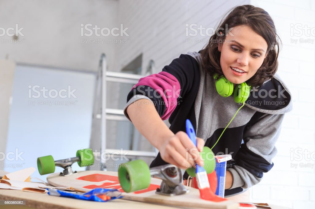 Young woman painting skateboard royalty-free stock photo