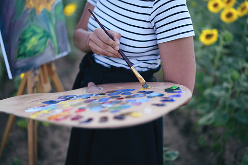 Young woman painting sunflowers outdoors