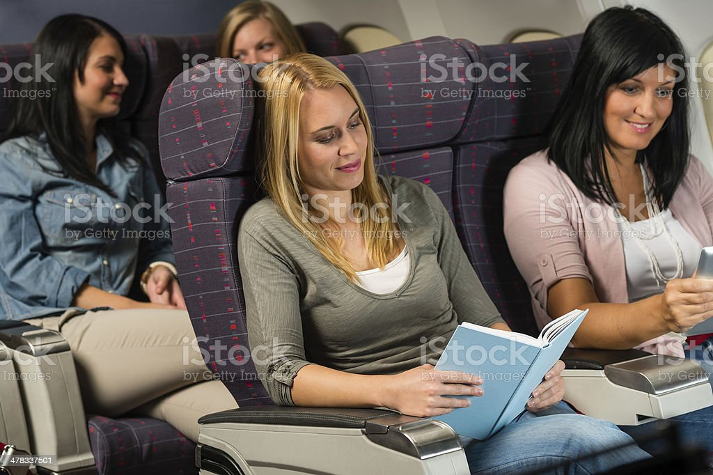 Young woman passenger read book airplane flight royalty-free stock photo
