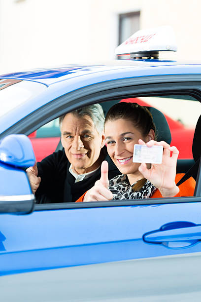 Young woman passing her drivers test and receiving license Driving School - Young woman steer a car, maybe she has a driving test, she holding proudly her driving license then she has passed driving instructor stock pictures, royalty-free photos & images