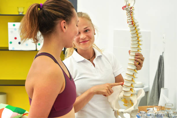 Young woman patient at physiotherapy consultation, physiotherapist explaining back bones on spine model stock photo