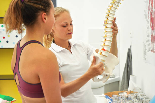 Young woman patient at physiotherapy consultation, therapist explaining her back bones on spine model stock photo