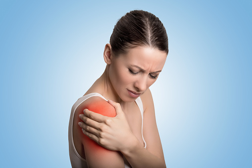 istock Young woman patient in pain having painful shoulder colored in red. 669684798